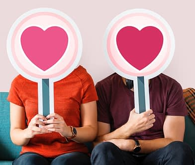 Two people on couch holding heart signs over their faces